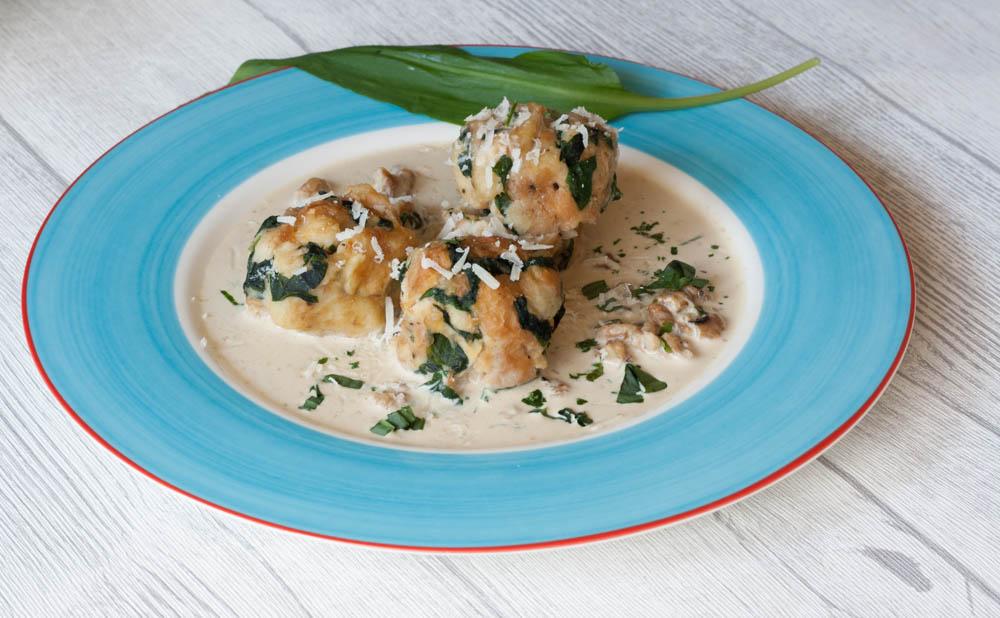 Bärlauchknödel mit Parmesansoße auf Teller