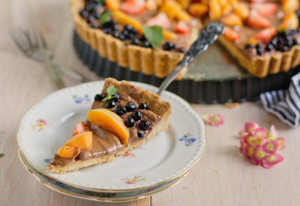 Kuchenstück Schokoladentarte mit Blaubeeren und Aprikosen