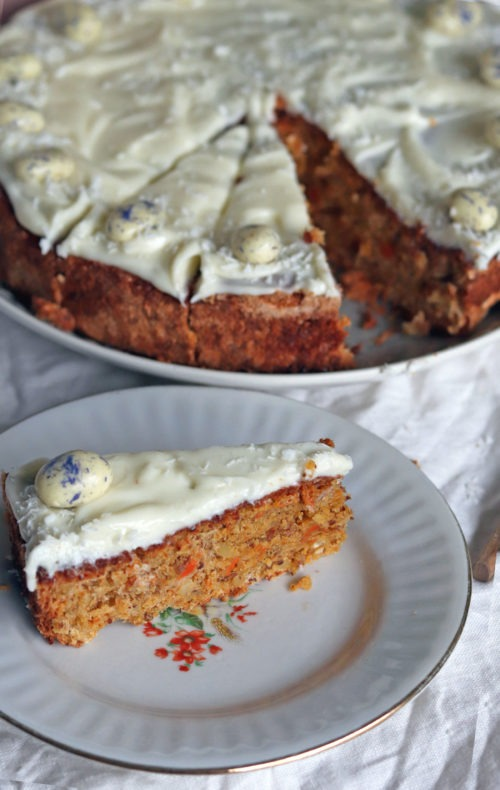 Stück Karottenkuchen mit Frischkäsetopping. Rüblitorte backen mit diesem einfachen Rezept. Perfektes Osterrezept total easy.